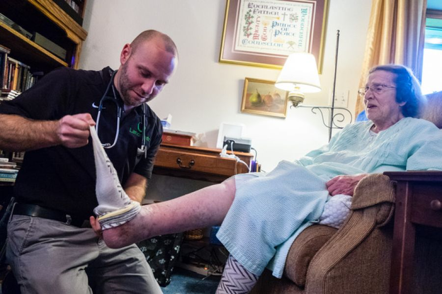 Dr. Phillip Dove examines 95-year-old Dorothea Preston's feet at her home in SE Portland.