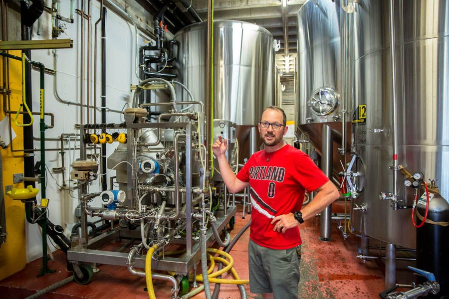 Christian Ettinger, founder of Hopworks Urban Brewery, stands in front of the water-reclamation tank at the company's first pub and brewery on Southeast Powell Boulevard in Portland.