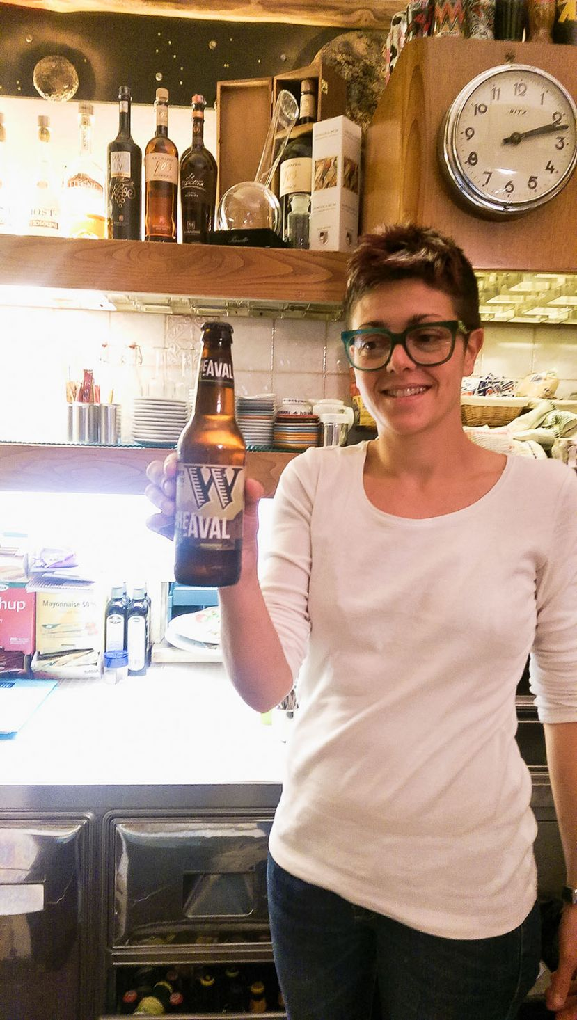A server in Tuscany displays a bottle of Widmer Upheaval IPA.